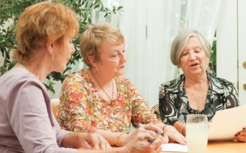 Three women looking at a paper